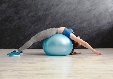 zena - trening s fitness loptou v telocvicni