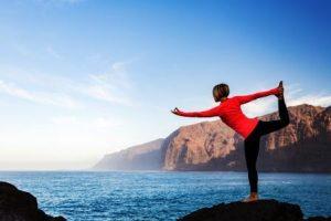 Žena meditujúci v tanečnici jogy póza (Natarajasana) cez oceán a pobrežie