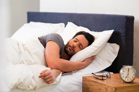 muž spí v posteli