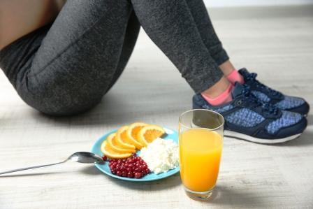 Žena sedí na podlaze a vedle sebe má zdravou snídani